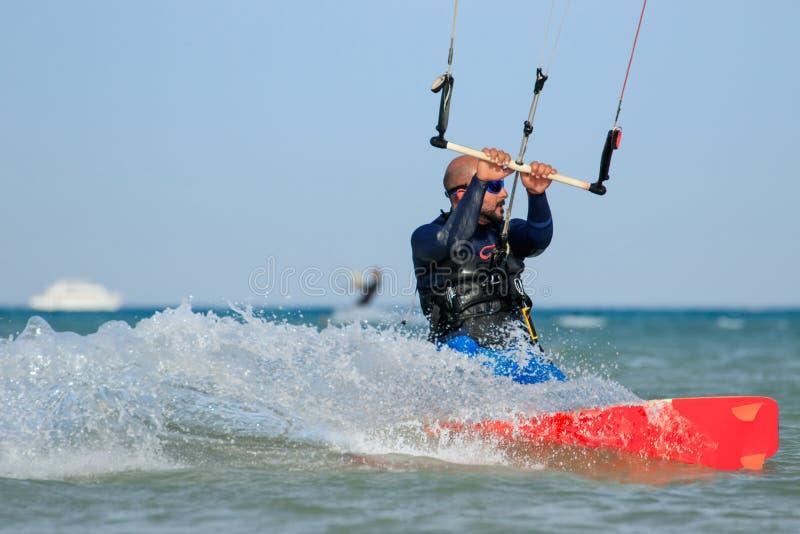 Der Berufsdracheneinstieg-Reitersportler mit Drachen reitet blaue Lagune l?chelnd, zeit Freizeit-Restes der Spa?freude genie?end  stockbild