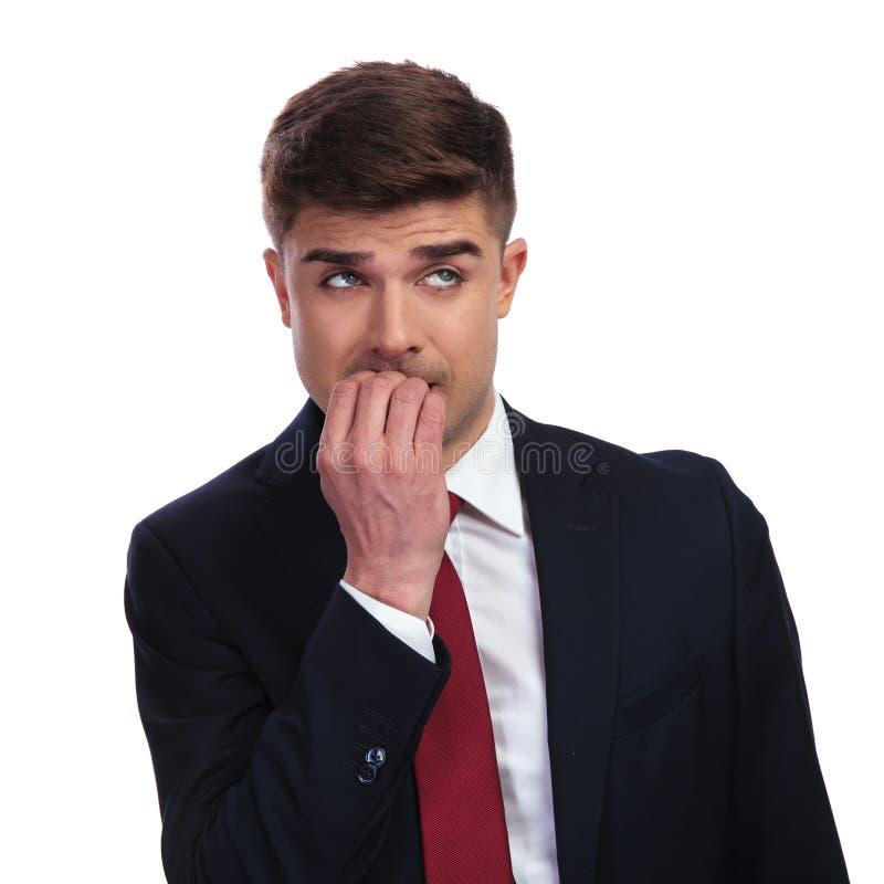 Der betonte Geschäftsmann, der seine Nägel beißt, schaut oben, um mit Seiten zu versehen stockbild