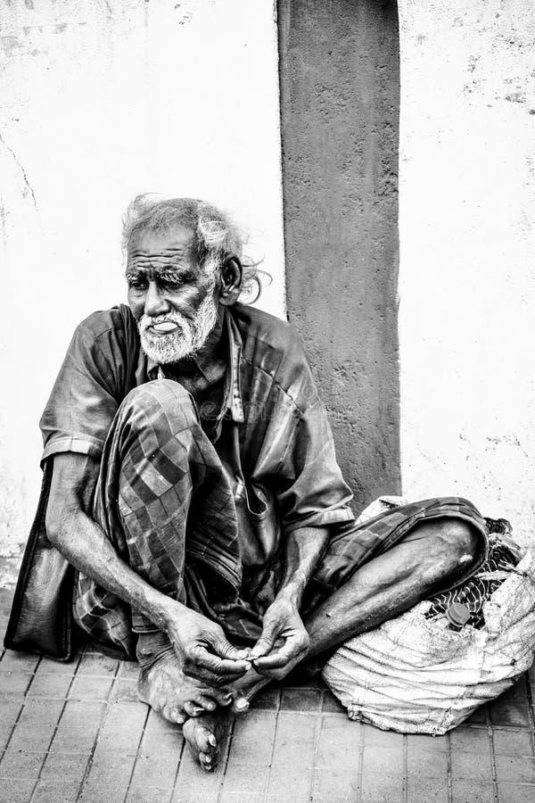 Der Bettler auf dem Fußweg stockbild