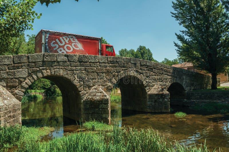 Der Bier-LKW, der über alte Brücke auf überschreitet, trennen Fluss in Portagem stockfotografie
