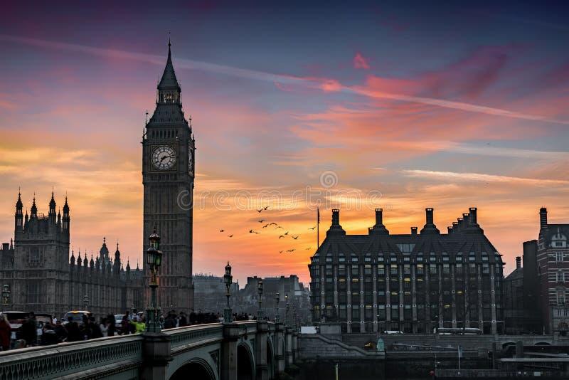 Der Big Ben-Turm und die Westminster-Brücke bei der Themse in London während der Sonnenuntergangzeit stockbild