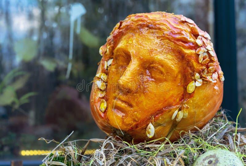 Der bildhauerische Kopf wird von einem orange Kürbis geschnitzt stockbild