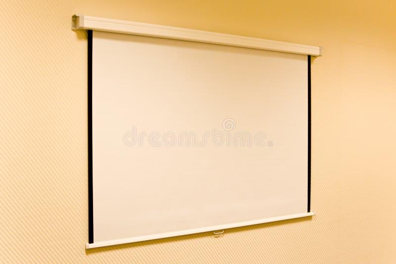 Der Bildschirm für einen Projektor auf einer Wand des Büros lizenzfreie stockfotos