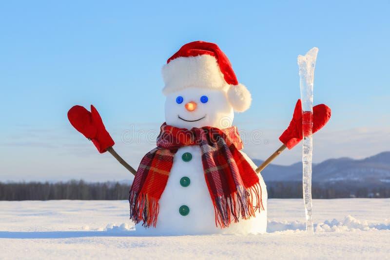 Der blauäugige lächelnde Schneemann im roten Hut, in den Handschuhen und im Plaidschal hält den Eiszapfen in der Hand Froher kalt stockbild