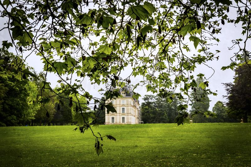 Der Blick auf das Schloss Cheverny, das Tal von Loire, Frankreich Die Aussicht von weitem durch die Äste stockfotos