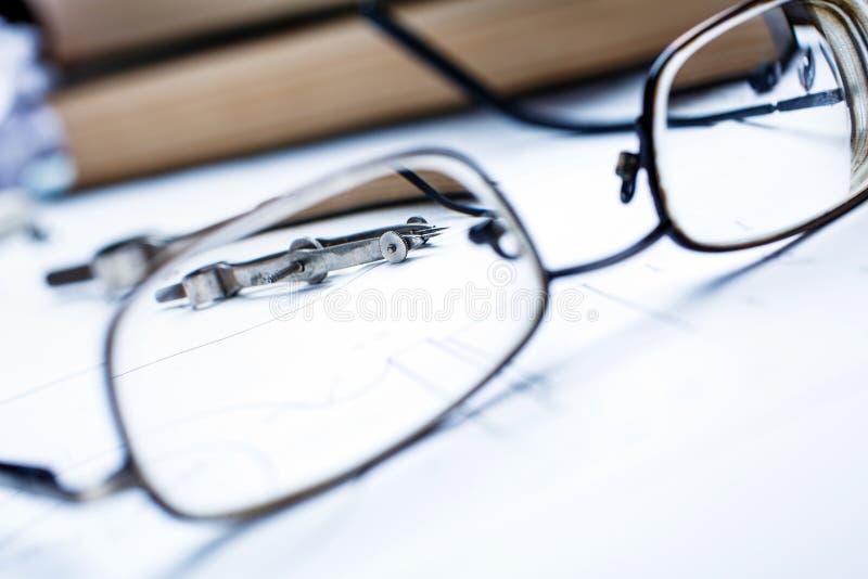 Der Blick des Kompassses durch die Gläser auf dem Hintergrund von Büchern auf Architektur stockfoto