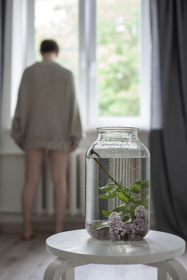 Der Blumenstrau? von lila Zweigen in einem transparenten gr?nen Glas auf dem wei?en Stuhl als Dekoration des Innenraums lizenzfreies stockbild