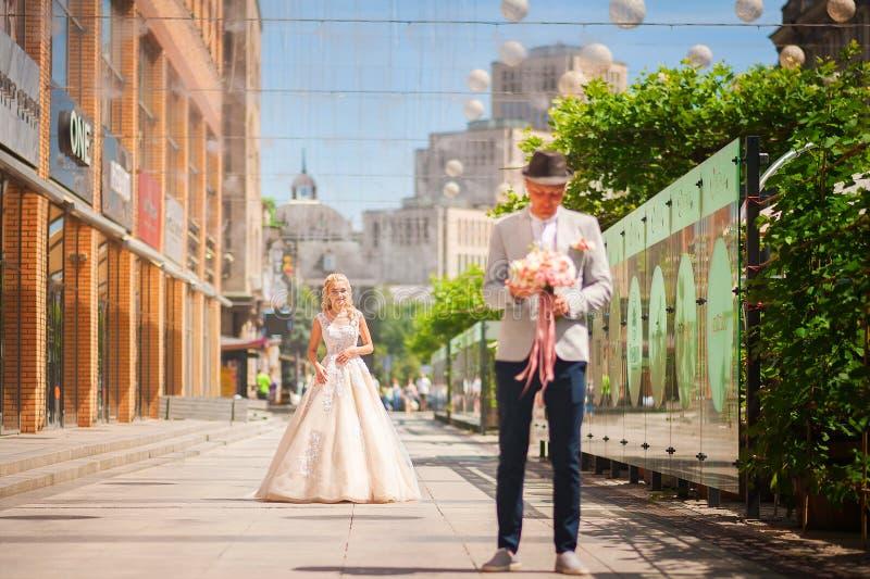 Der Bräutigam erwartet die Braut vor der Sitzung Liebendes Hochzeitspaar im Sommer auf dem Platz in der Stadt Dnipro, Ukraine stockfotografie