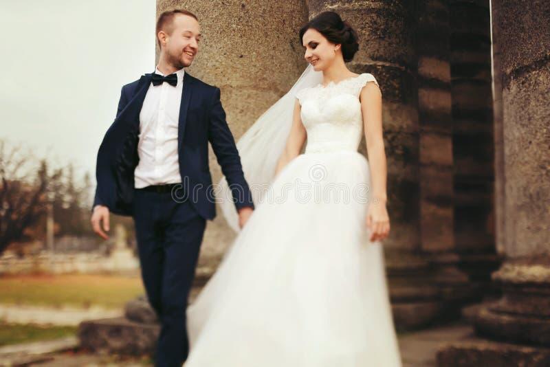 Der Bräutigam hält Braut ` s Hand gehend mit ihr von ruiniert cathed stockfotos