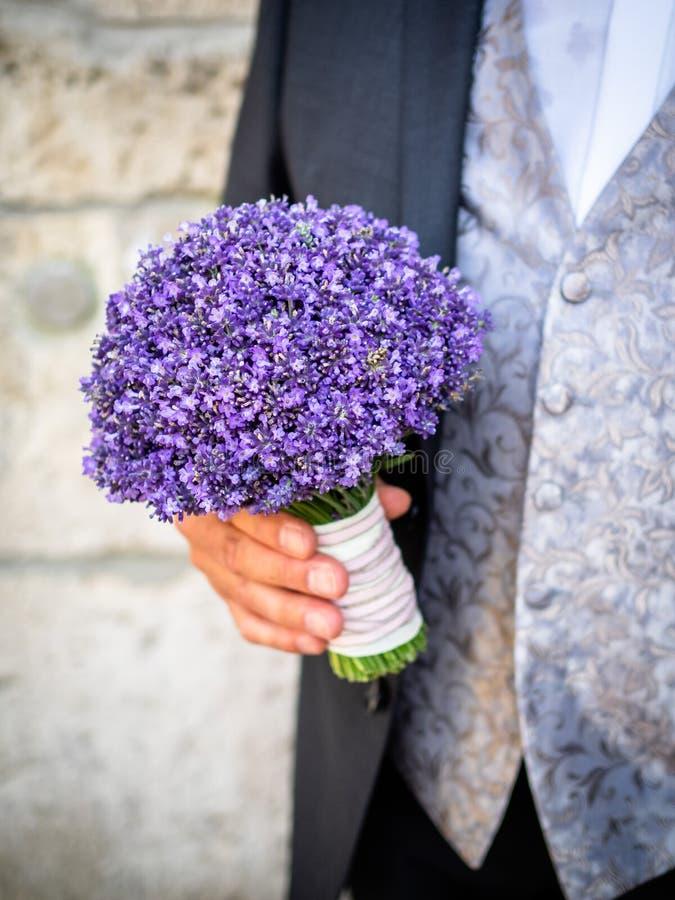 Der Bräutigam hält den Brautblumenstrauß lizenzfreie stockfotos