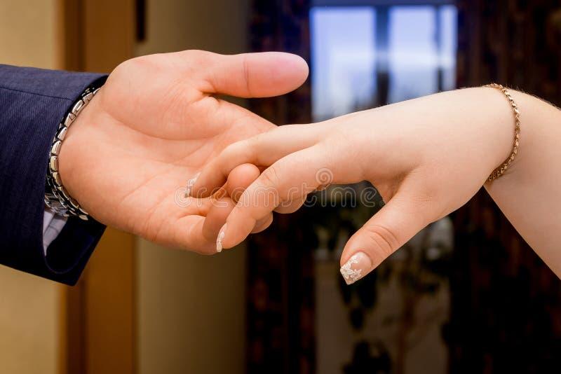 Der Bräutigam hält die Braut ` s Hand in ihrer Hand Glückliche junge Leute lizenzfreie stockfotos
