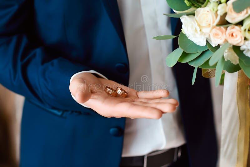 Der Bräutigam hält Goldeheringe in ihrer Hand Ein Bräutigam mit einem Blumenstrauß an der Hochzeit Das Konzept von Hochzeiten lizenzfreies stockfoto