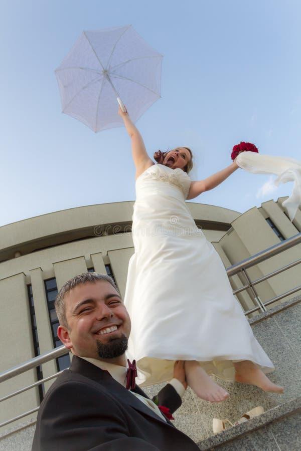 Der Bräutigam kann die Braut mit Regenschirm nicht entweichen stockbild