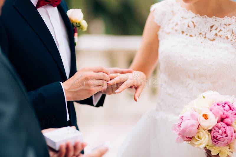 Der Bräutigam kleidet einen Ring auf dem Finger der Braut an einer Hochzeit lizenzfreies stockfoto