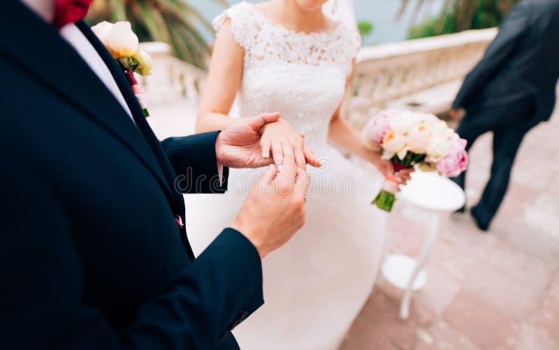 Der Bräutigam kleidet einen Ring auf dem Finger der Braut an einer Hochzeit lizenzfreies stockbild