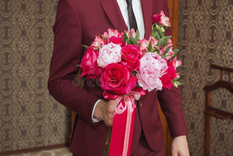Der Bräutigam mit Blumenstrauß geht zu seiner Braut lizenzfreies stockfoto