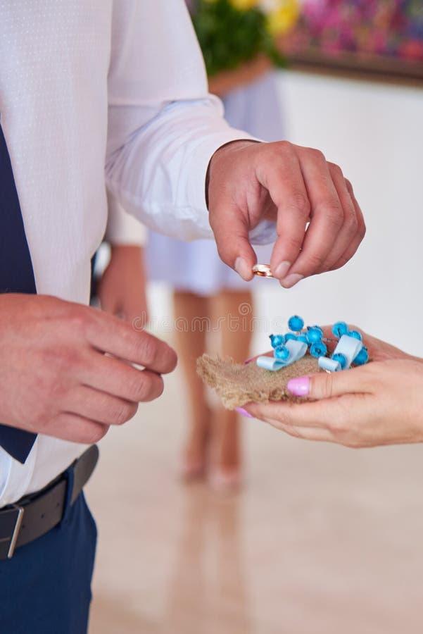 Der Bräutigam nimmt den Ring, um die Braut auf den Finger an der Trauung zu setzen stockfotos