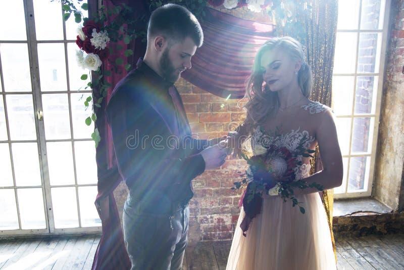 Der Bräutigam setzt den Ring auf die Braut an der Hochzeitszeremonie lizenzfreie stockfotografie