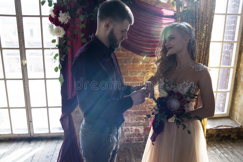 Der Bräutigam setzt den Ring auf die Braut an der Hochzeitszeremonie stockfotos