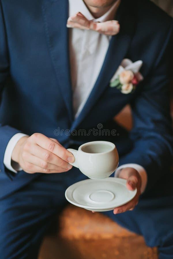 Der Bräutigam sitzt in einem blauen Anzug mit einer Fliege, hält eine weiße Schale in seinen Händen und trinkt Kaffee stockbilder
