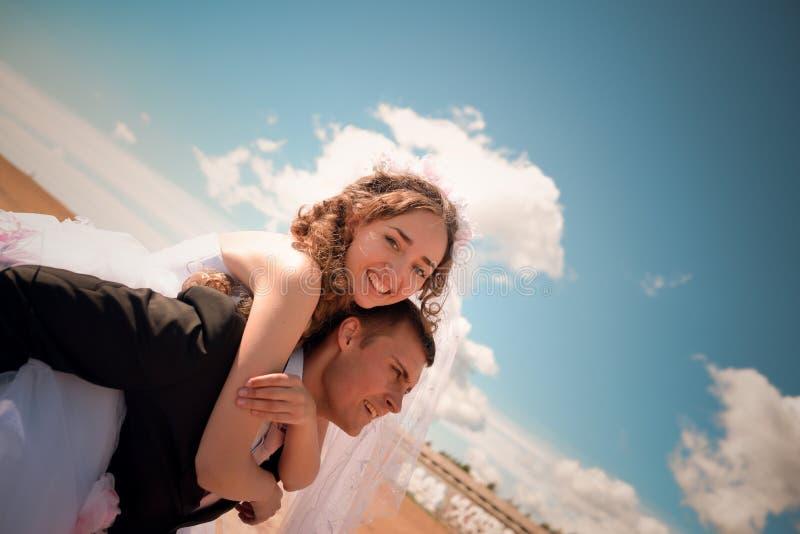 Der Bräutigam trägt die Braut auf einer Rückseite lizenzfreie stockfotos