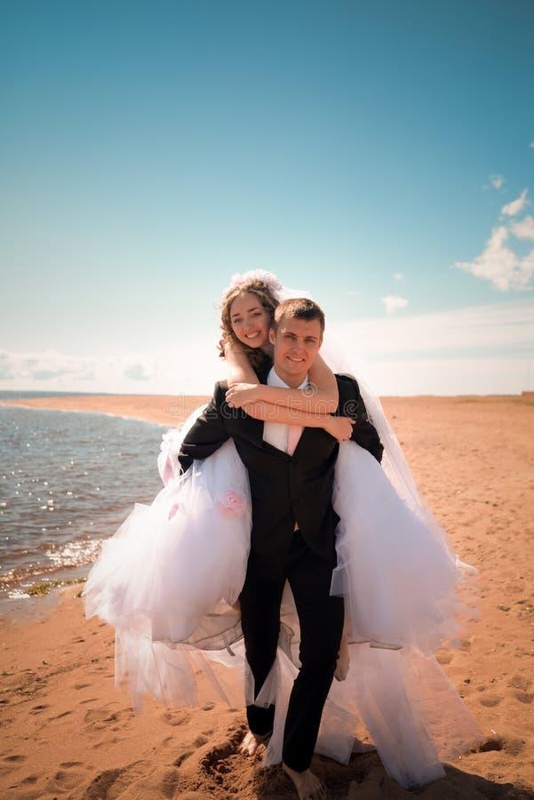 Der Bräutigam trägt die Braut auf einer Rückseite stockfoto