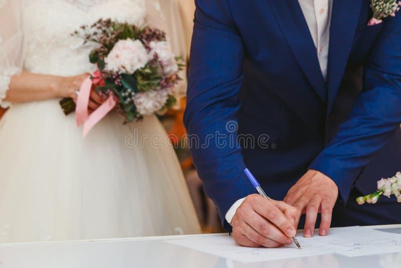 Der Bräutigam unterzeichnet die Hochzeit lizenzfreies stockfoto