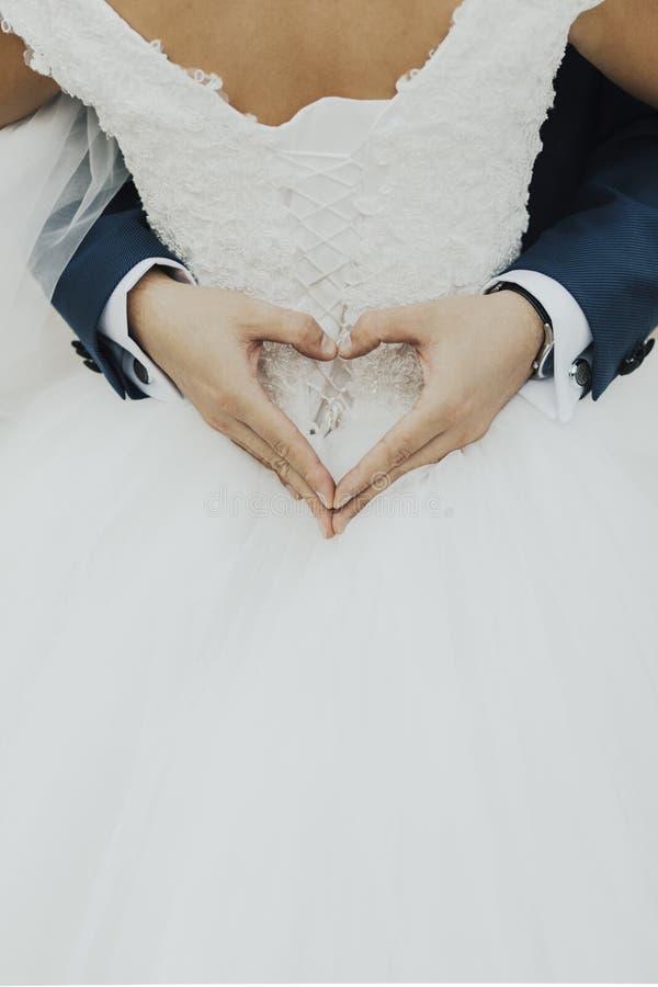 Der Bräutigam wurde in der Braut, die Hände des Bräutigams hatte ein Herz eingewickelt lizenzfreie stockfotografie
