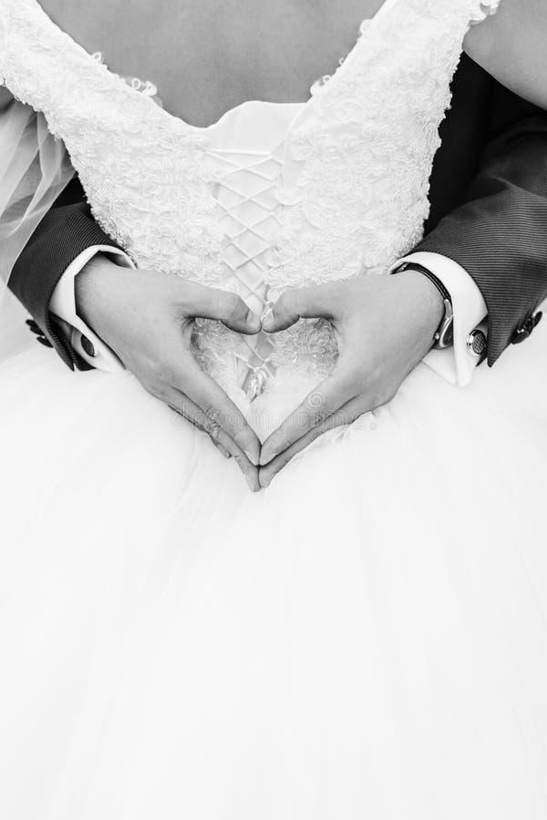 Der Bräutigam wurde in der Braut, die Hände des Bräutigams hatte ein Herz eingewickelt lizenzfreie stockbilder