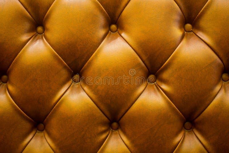 Der braune weiche Kunstlederhintergrund mit asymetrischen Knöpfen Weiche und teure M?belelemente Kann an Gru?karte, dekoratives P lizenzfreie stockfotografie