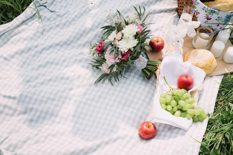 Der Braut ` s Blumenstrauß und die Frucht, die auf der Picknickdecke liegen stockfoto