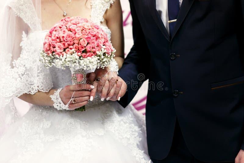 Der Brautgriff übergibt nahe Hochzeitsfahne stockbild