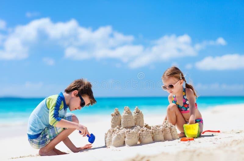 Zwei Kinder, die am Strand spielen stockfotos