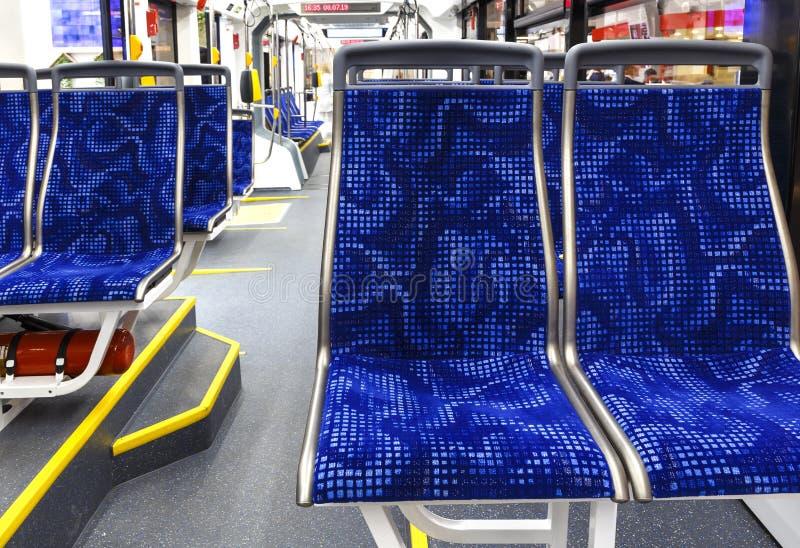Der Bus nach innen Innenraum des leeren modernen europ?ischen Stadtbusses mit blauen Sitzen und gelben Aufh?ngern stockfoto