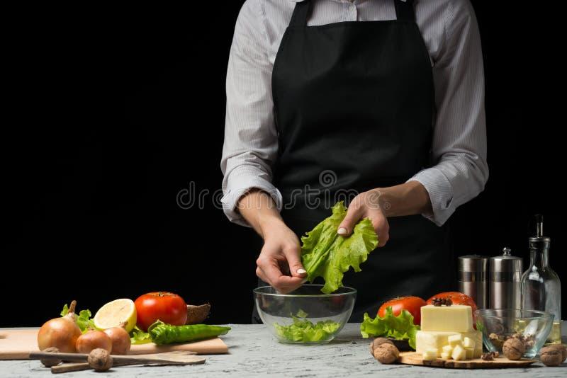 Der Chef bereitet einen Salat, gräbt oben Kopfsalatblätter, auf einem dunklen Hintergrund mit einem leeren Raum für eine Aufschri lizenzfreies stockfoto