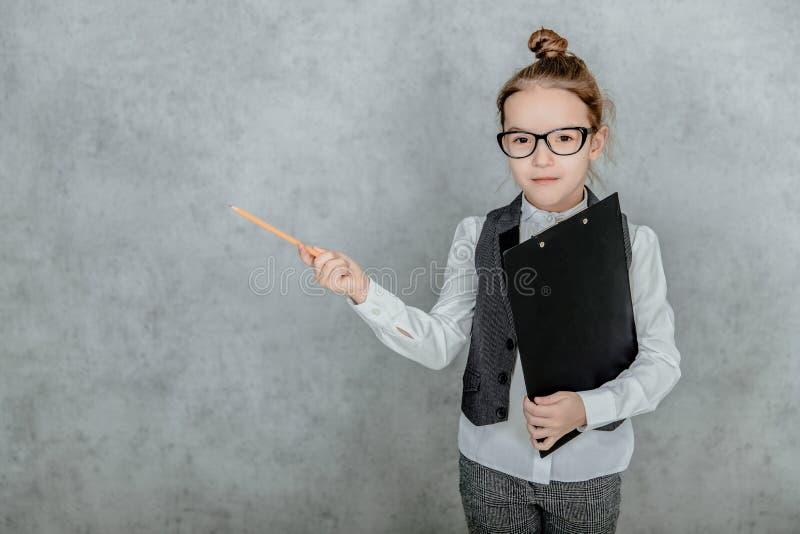 Der Chef der kleinen Dame ist auf grauem Hintergrund Dabei hält er einen schwarzen Ordner und hob den gelben Bleistift auf stockbilder