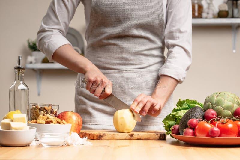 Der Chef kocht, Schnitte ein Apfel, bei einem vegetarischen Salat mit der Hand des Chefs in der Hauptküche leuchte lizenzfreie stockfotos
