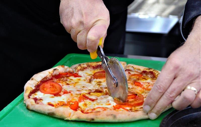 Der Chef schneidet die Pizza in Stücke für das Schmecken stockfotografie
