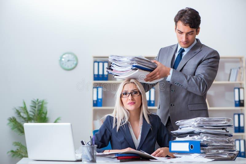 Der Chef, der seinem behilflichen Sekretär Mehrarbeit holt stockfotografie