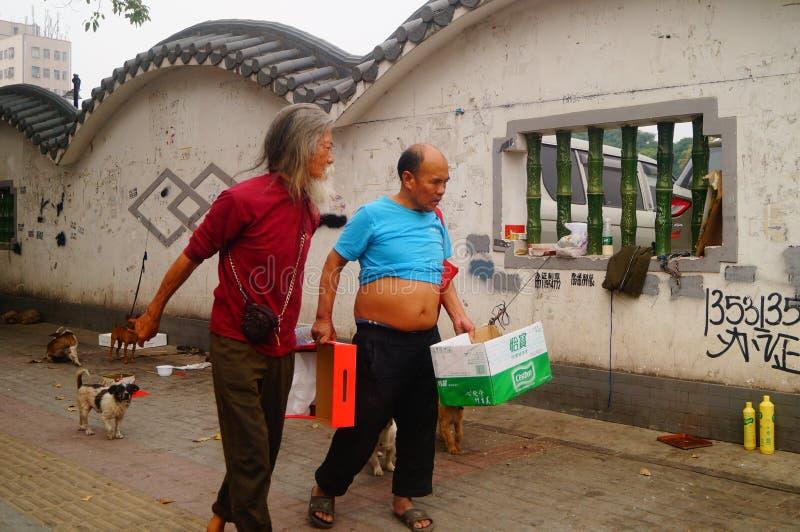 Der chinesische alte Mann in den streunenden Hunden lizenzfreie stockfotos