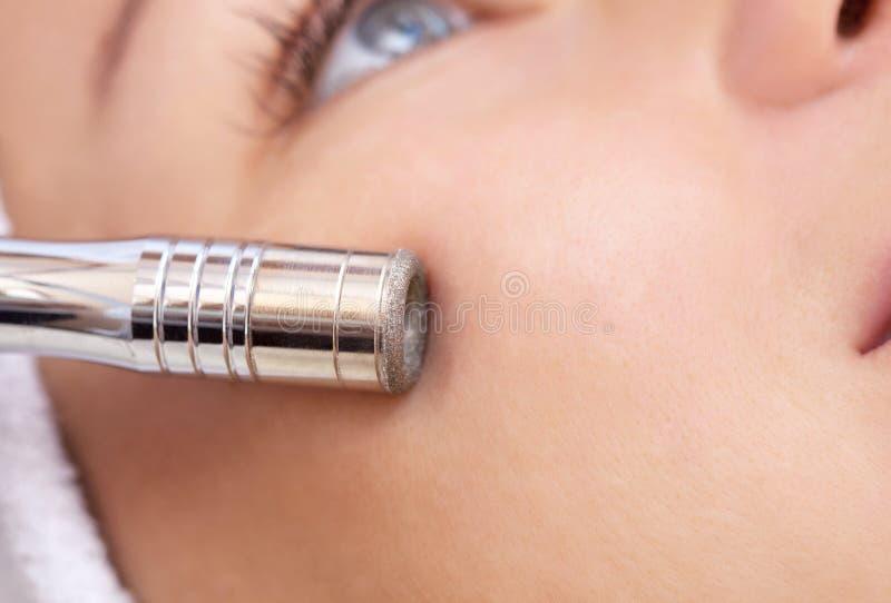 Der Cosmetologist macht das Verfahren Microdermabrasion von der Gesichtshaut einer schönen, jungen Frau in einem Schönheitssalon stockbild