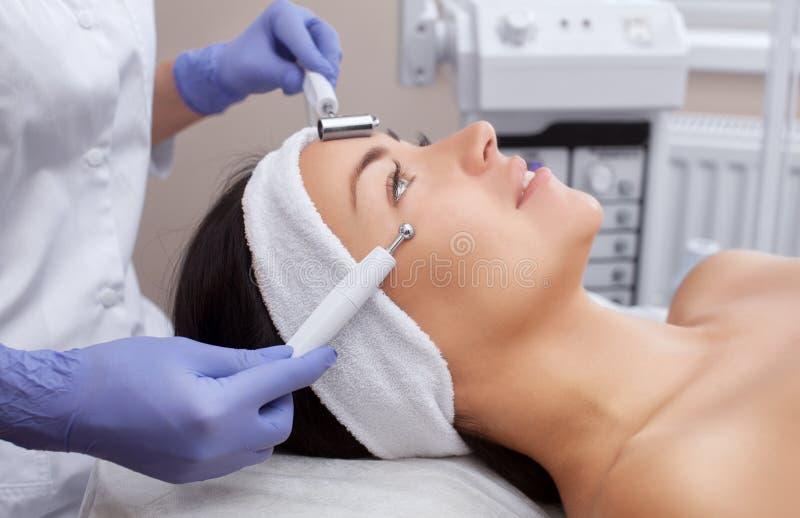 Der Cosmetologist macht den Apparat ein Verfahren von Microcurrent-Therapie einer schönen, jungen Frau in einem Schönheitssalon lizenzfreies stockbild