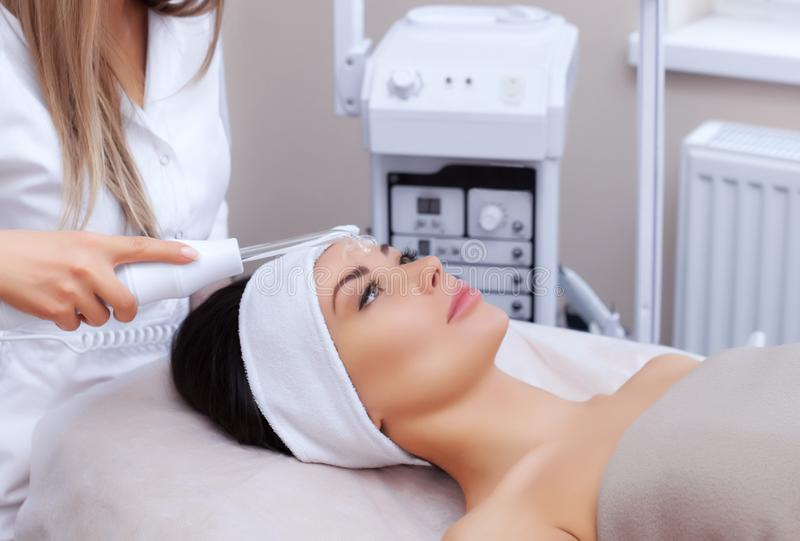 Der Cosmetologist macht die Verfahren Microcurrent-Therapie von der Gesichtshaut einer schönen, jungen Frau stockbild