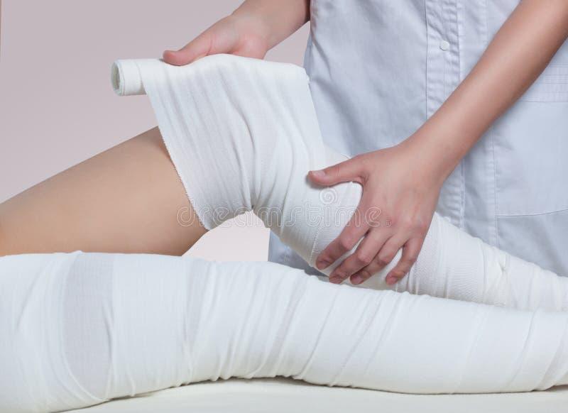 Der Cosmetologist wickelt das Bein des Kunden ein Anti-Celluliteverfahren stockfotos