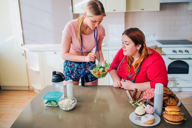 Der dünnen überladene vorbildliche Schüssel Frauen-Show Ypung mit slaad Stand in der Küche Zu Gewicht lösen oder nicht dilemma Ge lizenzfreie stockfotografie