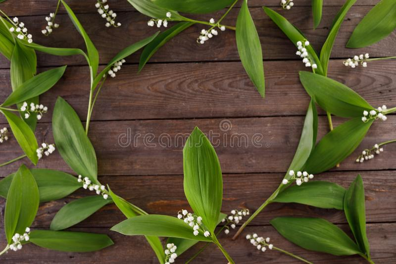 Der Dekor der Blumen des Maiglöckchens auf dem Hintergrund von hölzernen Brettern der Weinlese Weinlesehintergrund mit Rahmen von stockfotografie