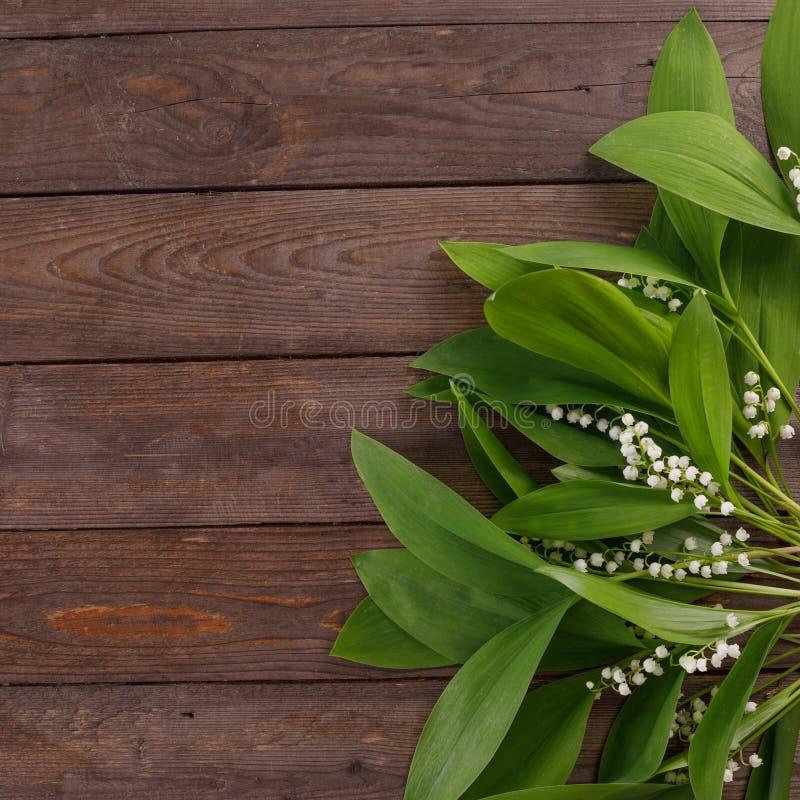 Der Dekor der Blumen des Maiglöckchens auf dem Hintergrund von hölzernen Brettern der Weinlese Weinlesehintergrund mit Rahmen von stockbilder