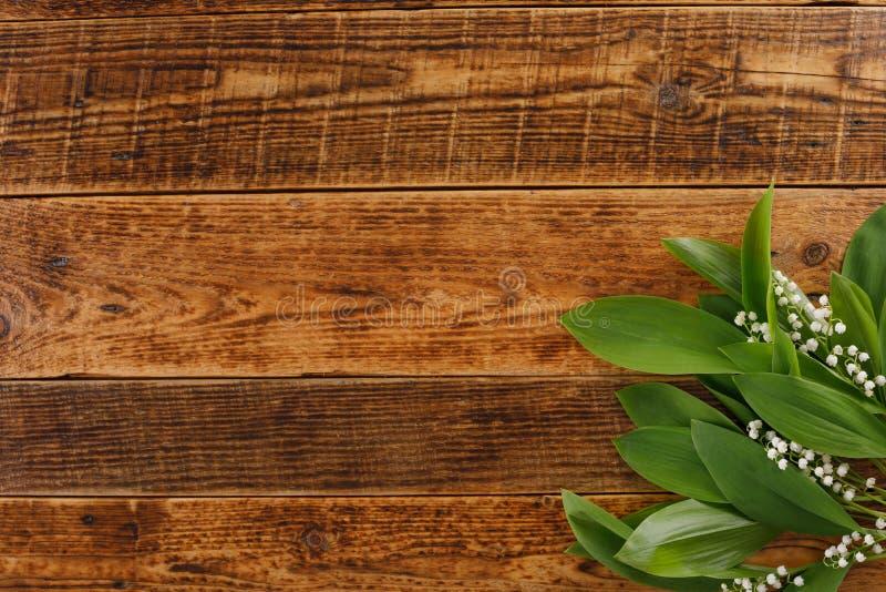 Der Dekor der Blumen des Maiglöckchens auf dem Hintergrund von hölzernen Brettern der Weinlese Weinlesehintergrund mit Rahmen von lizenzfreie stockfotos