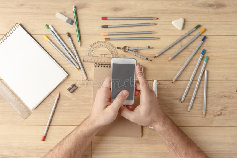 Der Designer zeichnet eine Skizze in einem Notizbuch auf einem Holztisch briefpapier Ansicht von oben stockfoto