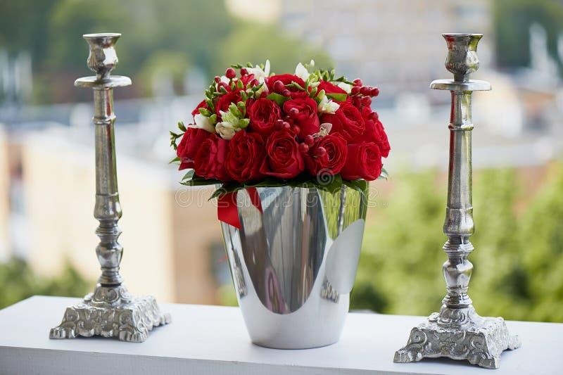 Der dichte rote Blumenstrauß von Rosen und von Beeren, glänzend im Eiseneimer zwei asphaltieren Kerzenhalter stockfotos